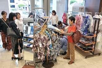 女性向けのかりゆしウェアを品定めする人たち=27日、那覇市・タイムスビル1階