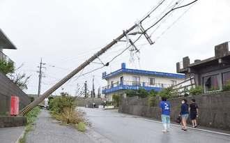 強い風で傾いた電柱。向かいの建物の窓ガラスは、飛んできたトタン屋根で破損した=17日午後3時48分、与那国町久部良(山田優介撮影)