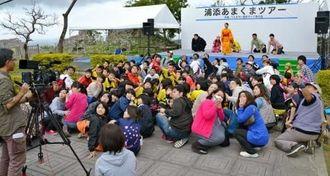 舞台上のキャスト(奧)と一緒に演技するエキストラ=26日、浦添城跡