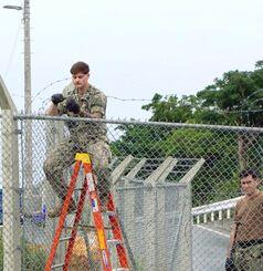 米軍普天間飛行場の金網フェンス上部の有刺鉄線を直す米軍関係者ら=10日、宜野湾市宜野湾