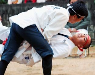 沖縄角力で対戦する吉原元太郎さん(下)と父親の徹さん。元太郎さんが2勝1敗で勝利した=23日、北大東村の秋葉神社(知花薫通信員撮影)