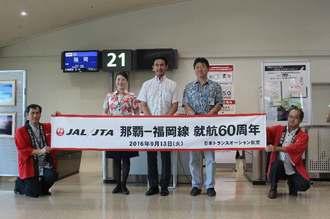 就航60周年を祝うJTAの丸川潔社長(中央)ら=13日、那覇空港ターミナルビル2階