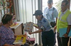 1人暮らしの高齢者に犯罪被害防止のパンフレットを渡す石川署の警察官ら=うるま市石川松島区
