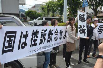 「国は控訴断念せよ」と書かれた横断幕と「勝訴」の垂れ幕を掲げる弁護士や支援者ら=6月28日、熊本地裁前