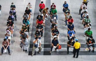 新型コロナウイルスワクチン接種会場の外に、マスクをして並ぶ市民=22日、バンコク(ロイター=共同)