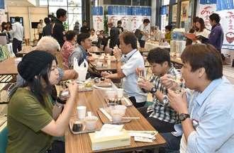 午前7時30分にオープンした「でいご食堂」で、玄米や白米のおにぎり、ライスグラノーラの朝食を食べる来場者=12日午前8時すぎ、那覇市久茂地・タイムスビル