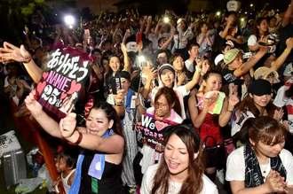 安室奈美恵さんの歌を合唱する、ライブ会場に入れなかったファンたち=15日午後8時48分、宜野湾海浜公園(金城健太撮影)