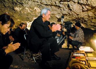 ガマの中に設けられた祭壇に手を合わせ、犠牲者の冥福を祈る遺族の與那覇徳市さん(中央)ら=1日午後1時15分、読谷村波平・チビチリガマ