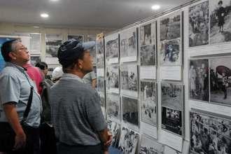 大田昌秀さんが集めた沖縄戦の写真に見入る来館者=29日、那覇市西・沖縄国際平和研究所