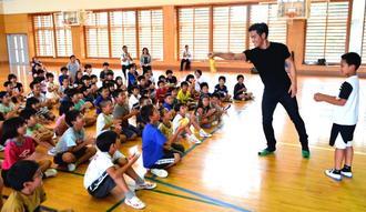 未開封のペットボトル飲料の中に入った児童のサイン入りカードを示すMASAさん(右から2人目)=6日、名護市立稲田小学校