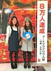 8万人目となった前粟蔵亜樹さん(右)と長濱多喜子さん=5日、那覇市・デパートリウボウ