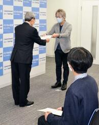 内閣官房の幹部(左)から辞令を受け取る職員=12日午前、東京都港区