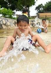 強い日差しの中、公園の噴水で遊ぶ子どもたち=7日午後、金武町・大川児童公園(喜屋武綾菜撮影)
