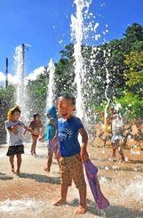 冷たい噴水を浴び、喜ぶ子どもたち=3日午後3時半、金武町・大川児童公園(国吉聡志撮影)
