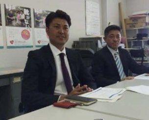 履かなくなった子ども用靴の寄付を募る赤嶺昇代表理事(右)と比嘉寿光理事