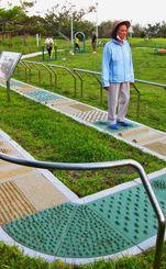 凹凸の付いた「歩道」をゆっくりと歩く市民。他の健康器具も多くの人が利用する=那覇市古波蔵・漫湖公園