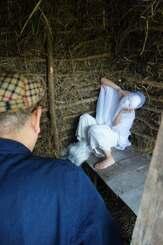再現された小屋の中で撮影する原義和監督(手前)とDanzatakara.さん=20日、八重瀬町