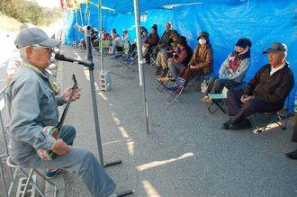 三線を披露する島田忠彦さん(左)=13日午前、名護市辺野古の米軍キャンプ・シュワーブゲート前