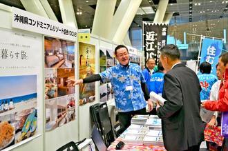 沖縄の魅力を説明する県コンドミニアムリゾート協会の川口達也事務局長(中央)=26日、東京・有楽町の東京国際フォーラム