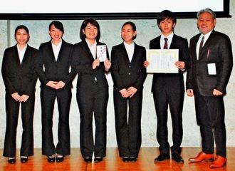 最優秀賞に選ばれた名桜大学の学生らと平良朝敬会長(右)=12日、宜野湾市、沖縄コンベンションセンター