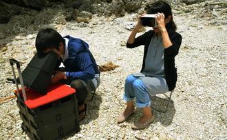 VRゴーグルを着けて、水中ドローンの操縦士(左)が映す映像でシュノーケリングを疑似体験する女性=19日、宮古島市伊良部の海岸