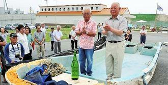 東日本大震災の津波で漂流し、糸満に流れ着いた漁船の船首に、お神酒を供えて手を合わせる所有者・松川一雄さん(右)と船の管理をするNPO法人ハマスーキの上原謙理事長=30日、糸満海のふるさと公園