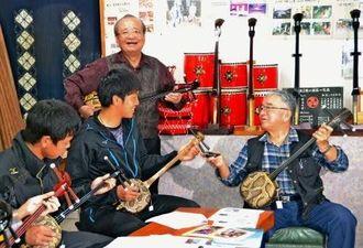 (右から)三線の弾き方を教える慶佐次興達さん、新城伸治さん、ヤクルトの原樹里投手、山崎晃大朗外野手=5日、浦添市大平の新城工作所