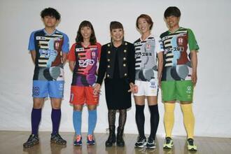 INAC神戸が新ユニホームを発表し、選手とともに写真撮影に応じるコシノヒロコさん(中央)=15日、神戸市