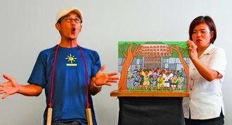 金丸が尚円王になり、村人が喜ぶラストシーンを読み聞かせする佐渡山安博さん(左)=西原町役場教育長室