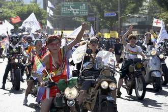 性的少数者への理解を訴え行われたパレードにバイクで参加する人々=14日、ソウル(共同)