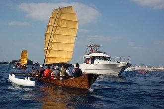大浦湾を航行する帆かけサバニと警戒しに来た巡視船=15日午前10時半ごろ、名護市大浦湾
