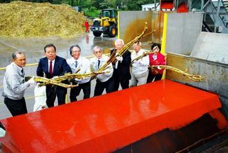 操業開始式で安全を願ってサトウキビを機械に投げる関係者=1日、宮古島市の宮古製糖伊良部工場