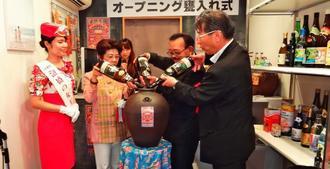 かめに泡盛を注ぎアンテナショップの開設を祝う県酒造組合の玉那覇美佐子会長(左から2人目)ら=4日、東京・品川区の同ショップ