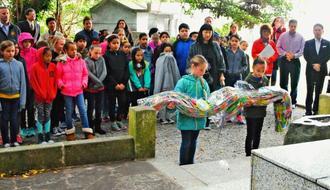 千羽鶴を手向けるキンザー小学校の児童=9日、浦添市の「前田高地平和之碑」