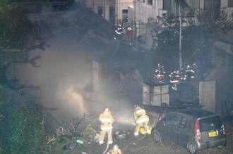 民家火災で消火活動をする消防隊員=6日午前2時27分、那覇市繁多川