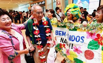 知人らに出迎えられ、笑顔を見せる94歳の當山正雄さん(左から2人目)=25日、那覇空港国際線ターミナル(渡辺奈々撮影)