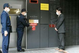 二酸化炭素の消火設備付近で緊急安全指導する東京消防庁の職員(左側)=23日午前、東京都港区