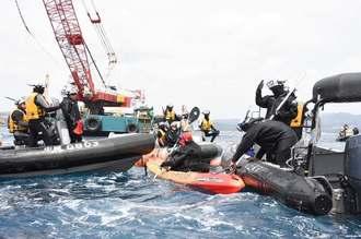 抗議のカヌーを拘束する海上保安官=29日午前、名護市辺野古のキャンプ・シュワブ沖