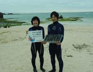 背後の海にこれから植え付ける36株のシコロサンゴを持つ、すみだ水族館の職員=2日午後、読谷村高志保