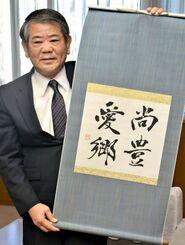 座右の銘「尚豊愛郷」の書を掲げる照屋義実副知事=11日県庁