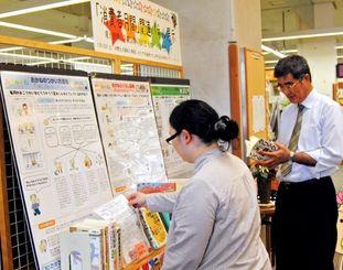 消費者月間パネル展。関連図書など約50冊が並べられている=那覇市寄宮・県立図書館