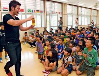 「ペットボトルにトランプが入ってるー!」。MASAさんのマジックに歓声を上げる子どもたち=21日午前、糸満市・真壁小学校(渡辺奈々撮影)