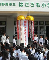 はごろも小学校の開校式で、くす玉を割る子どもたち=5日午前、宜野湾市大山の同校