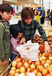 ジャガイモやタマネギなど北海道の特産品を買い求める来場者=日、那覇市久茂地・タイムスビル1階エントランス