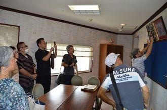 ハピナハ9階の旧社長室にある沖縄三越の写真の説明受ける参加者ら