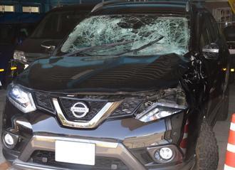 バイクと衝突し、窓ガラスが割れるなど損壊した米軍属の車両=26日、沖縄署