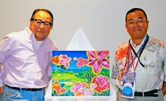 カヌチャリゾートをテーマにした新作を披露するヒロ・ヤマガタ氏(左)と白石武博社長=27日、名護市安部・カヌチャリゾート