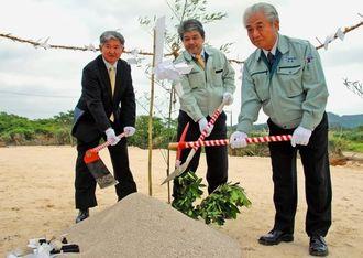 起工式でくわ入れする長濱社長(左)ら関係者=4日、本部町豊原の上本部飛行場跡地