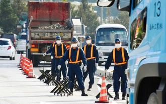 琉球セメントの桟橋に向かう右折レーンを規制する機動隊員=20日、名護市安和