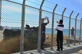 横断幕とリボンの撤去を進める日本人警備員(左端)のすぐ背後を通過する米軍の水陸両用装甲車=31日午前9時すぎ、名護市辺野古の浜